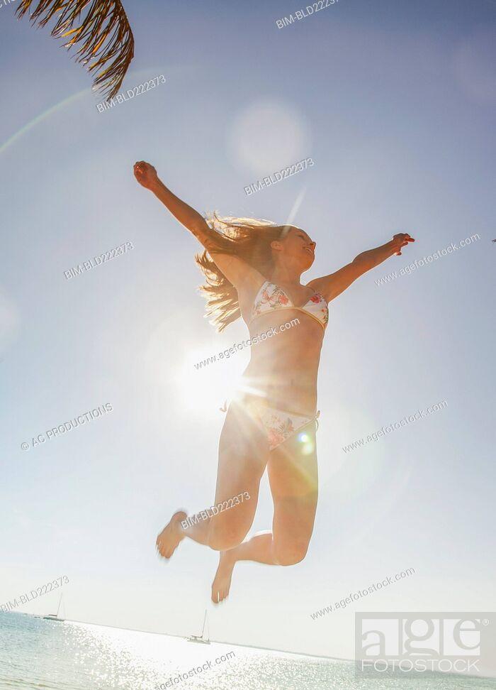 Stock Photo: Caucasian woman in bikini jumping for joy.