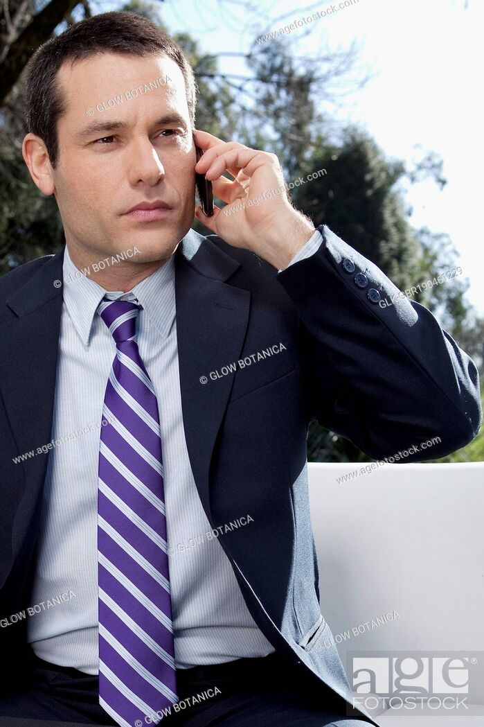 Stock Photo: Businessman talking on a mobile phone in a park.