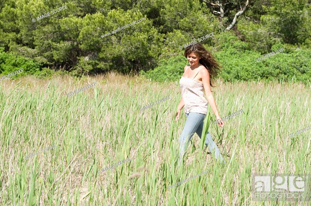 Stock Photo: Young woman walking through field.