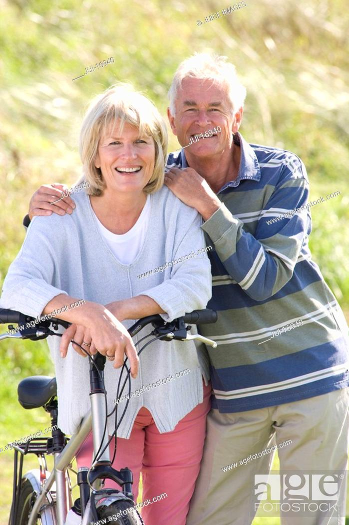 Stock Photo: Portrait of senior couple leaning on bicycle.