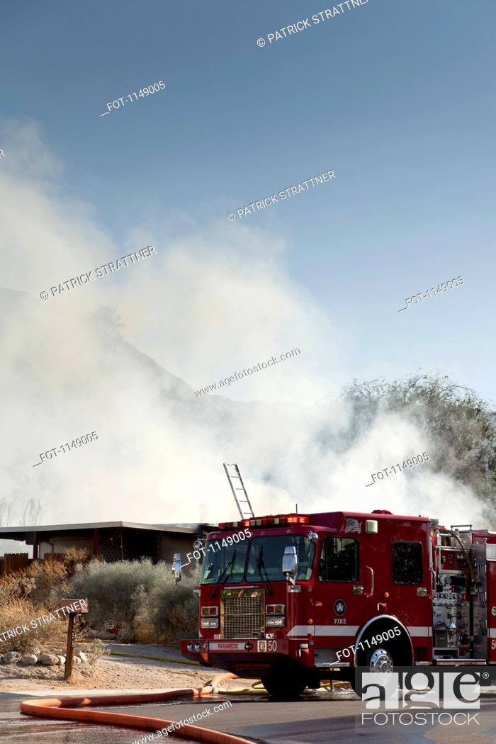 Stock Photo: A fire truck next to a burning house in a suburb.