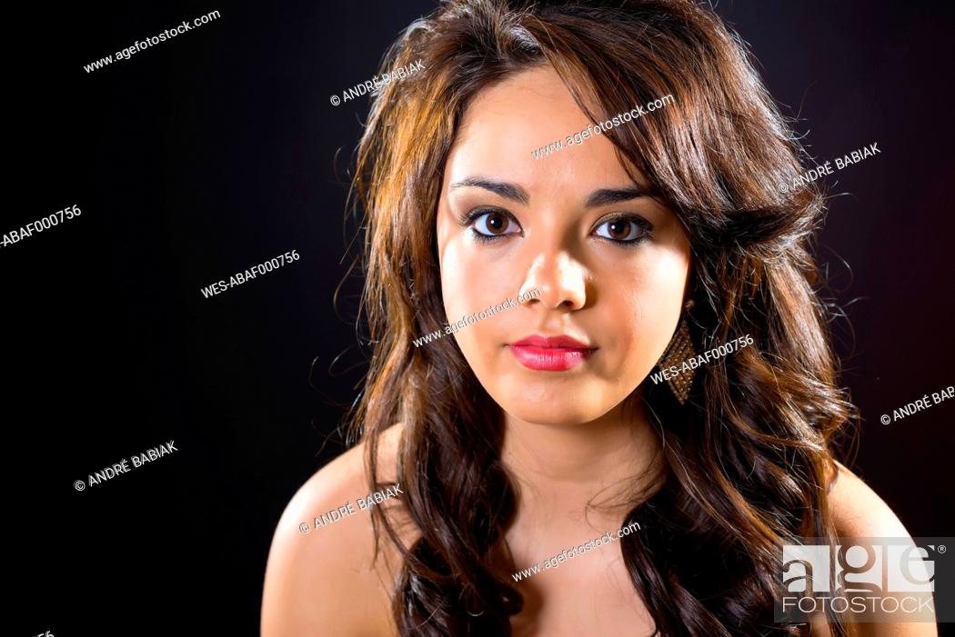 Stock Photo: Portrait of teenage girl against black background, close up.