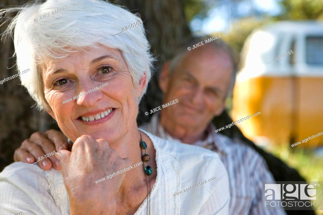 Stock Photo: Portrait of senior couple, man's hand on woman's shoulder, smiling focus on woman.