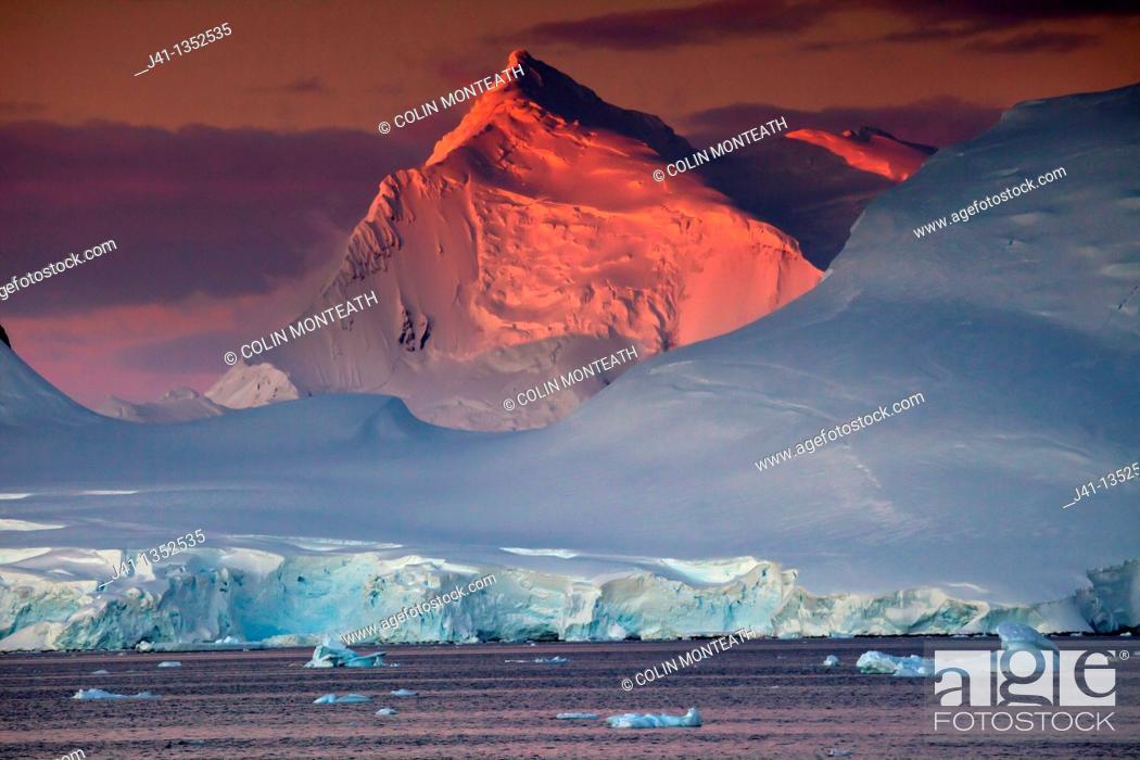Stock Photo: Alpenglow lights up high peaks on Wiencke and Anvers Islands behind Port Lockroy, Antarctic Peninsula.