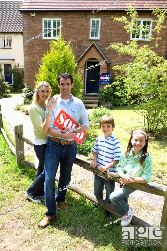 Stock Photo: Family of four by fence by house, father holding 'sold' sign, smiling, portrait.