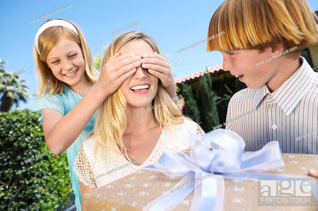 Stock Photo: Daughter covering eyes of mother who's receiving Gift from her Children outside.