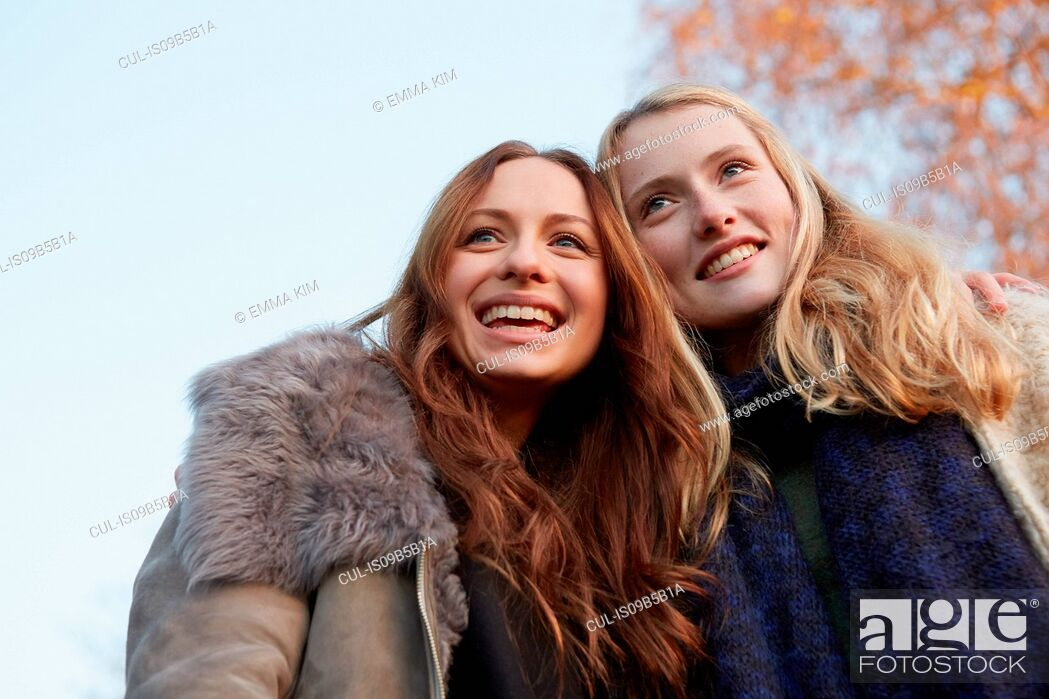 Stock Photo: Two female friends, walking outdoors, smiling.