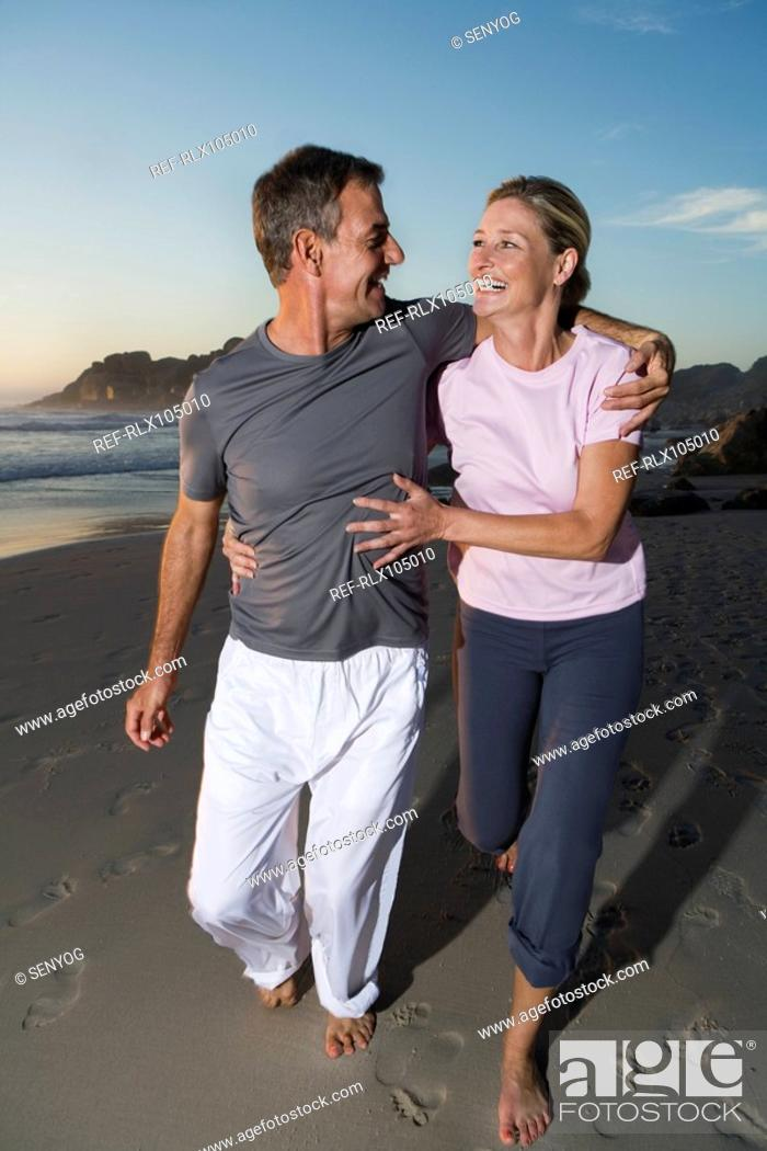 Stock Photo: Senior couple laughing while jogging along beach at sunset.