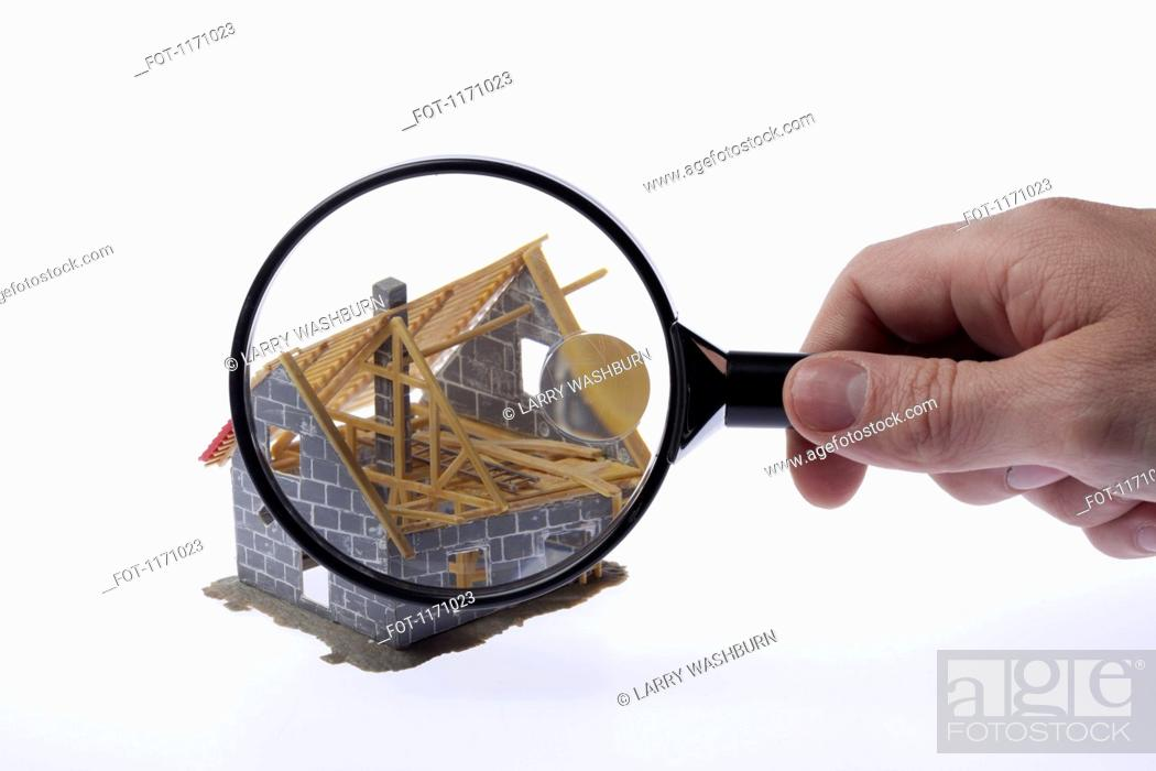 Stock Photo: A human hand holding a magnifying glass up to a partially constructed miniature house model.