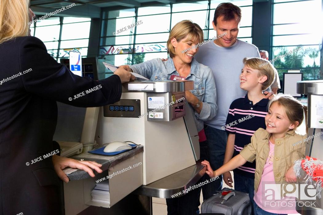 Stock Photo: Family checking in at airport check-in counter, woman passing tickets to female airline check-in attendant, smiling.