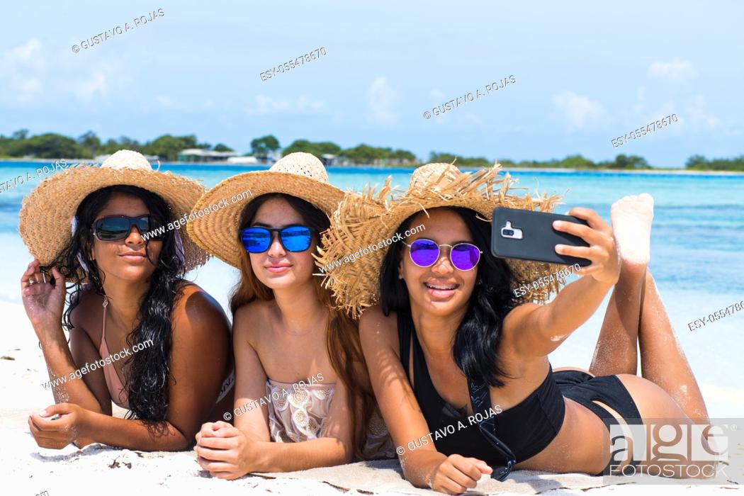Stock Photo: multiracial women friends together enjoy taking selfie photo at caribbean beach at Los Roques Venezuela.