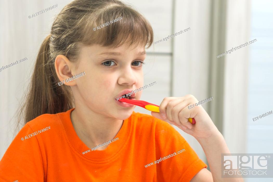 Stock Photo: The girl is brushing her teeth in the bathroom.