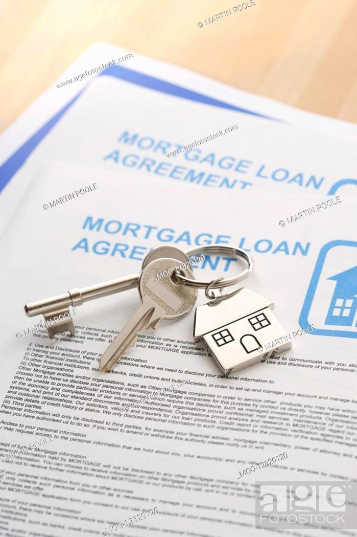 Stock Photo: Keys to a New Home and mortgage papers on table.
