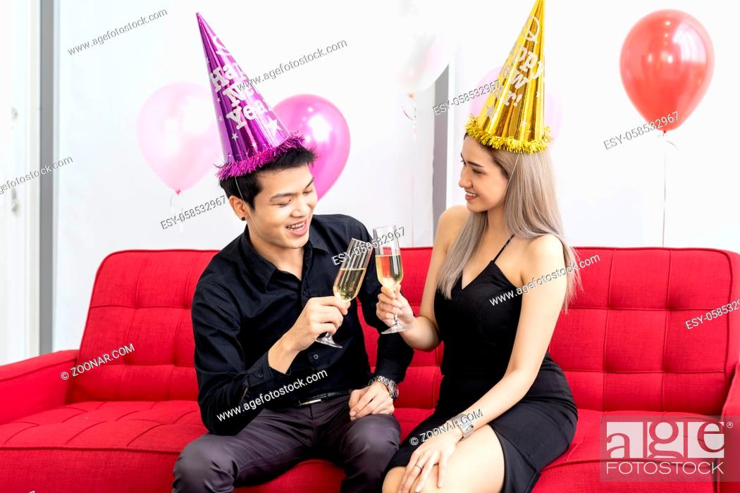 Photo de stock: Young asian adult couple celebrating New year christmas holiday with sparkling wine together in living room of big condominium in big city.