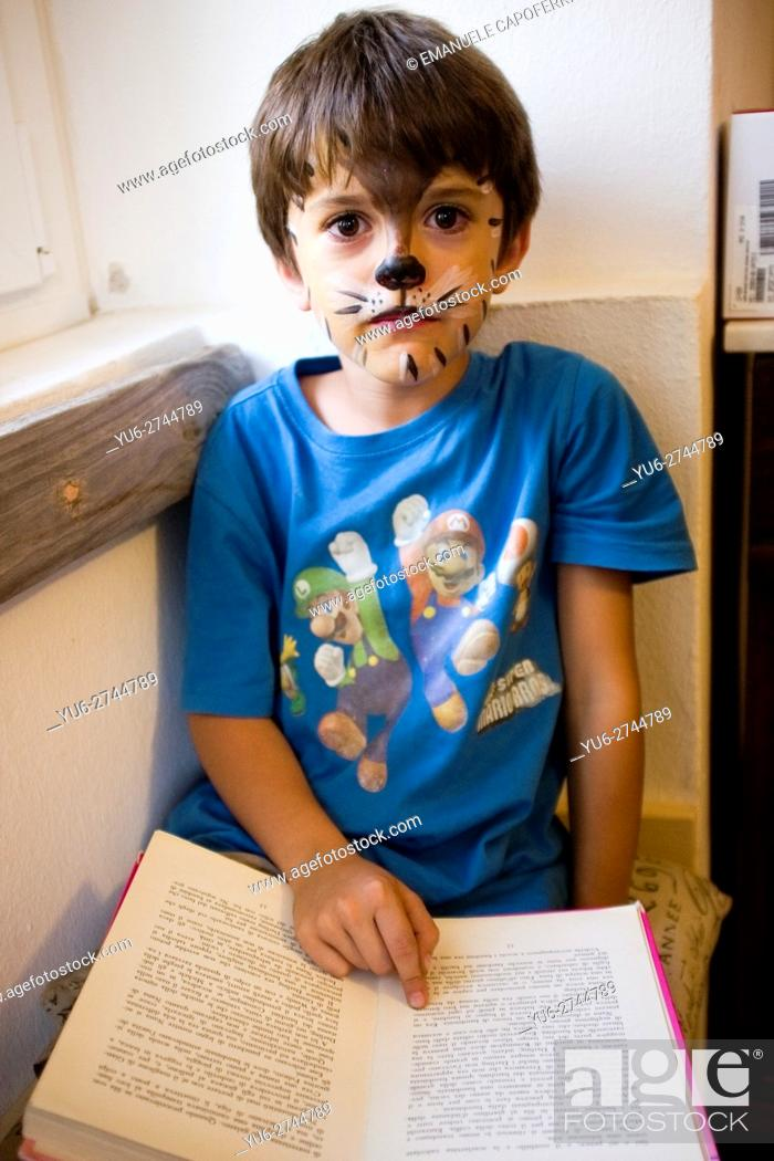 Stock Photo: 7 year old rigged as a cat reads a book near the window of the house.