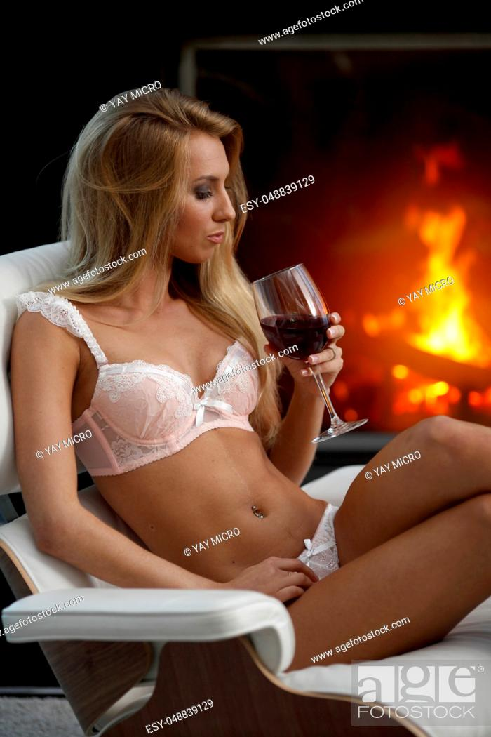 Stock Photo: Sexy woman in lingerie with wine near fireplace.