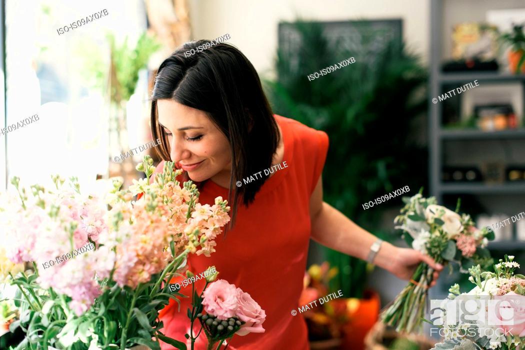 Stock Photo: Florist smelling flowers in flower shop.