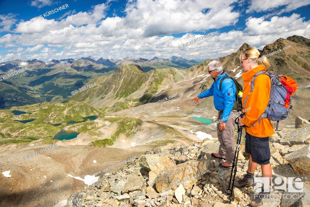 Stock Photo: Two hikers on the Fuorcia da Barcli pass, overlooking the Macun Lakes, Swiss National Park, Graubünden, Switzerland.