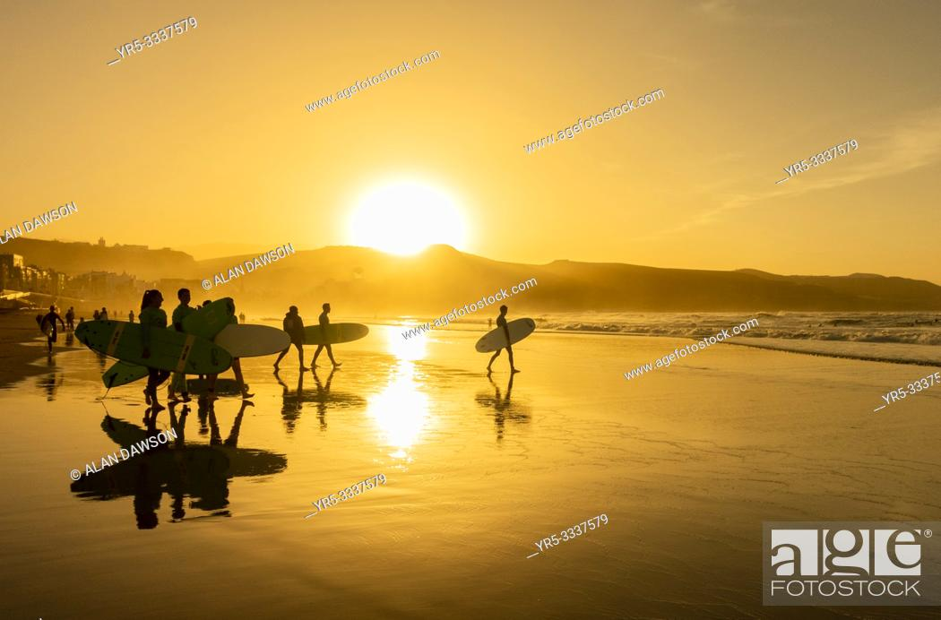 Stock Photo: Surfers at sunset on city beach at La Cicer, Playa de Las Canteras, Las Palmas, Gran Canaria, Canary Islands, Spain.