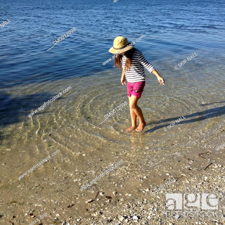 Imagen: Little girl wading through the water at the beach.
