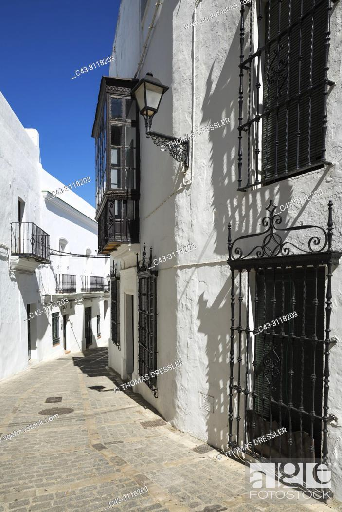 Stock Photo: Alleyway and brilliantly whitewashed, reja (grille) fronted houses in the hill-top town of Vejer de la Frontera. Cadiz province, Andalusia, Spain.