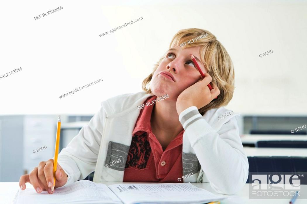 Stock Photo: School boy 10-13 sitting at desk in classroom thinking,.