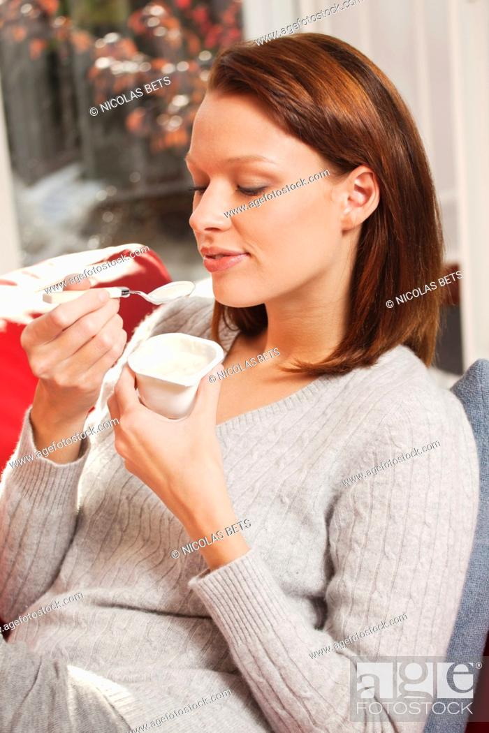 Stock Photo: Young woman eating a yogurt.