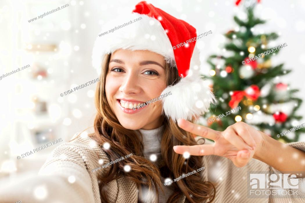 Stock Photo: happy woman taking selfie over christmas tree.