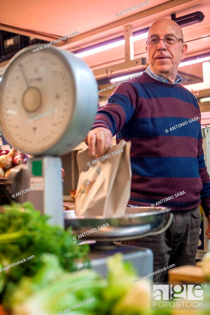 Stock Photo: Shopkeeper weighing fresh produce in market.