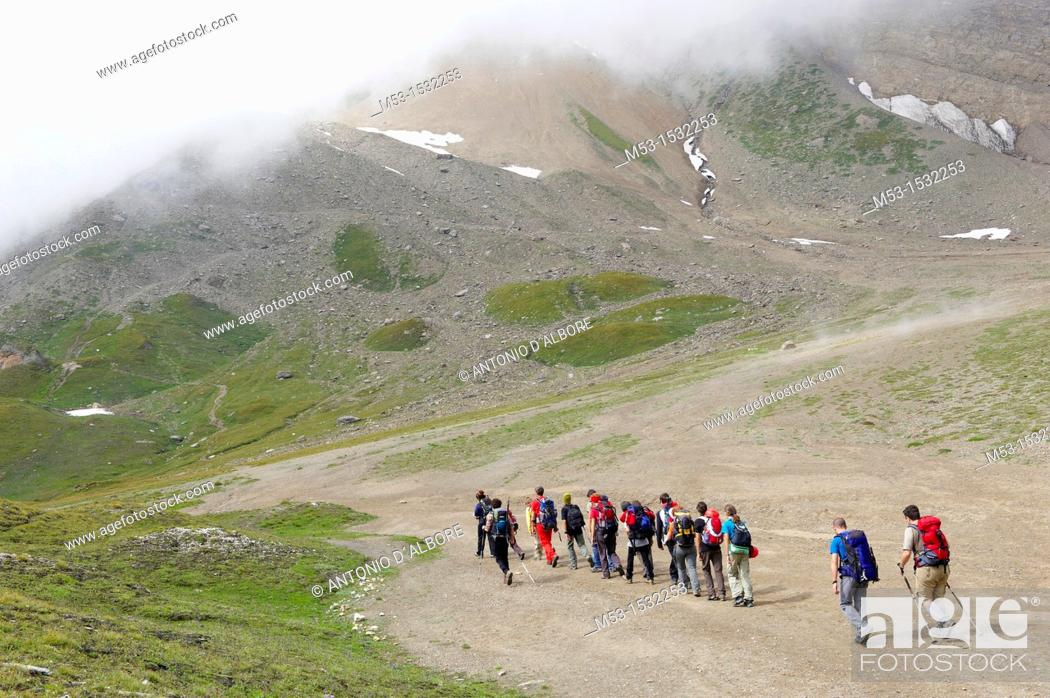Stock Photo: A group of hikers in single line formation cross the plateau called Piano dei Camosci, Lepontine Alps  Formazza  Italy.
