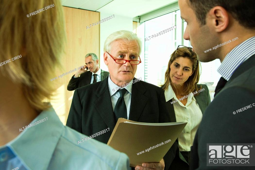 Stock Photo: Executives discussing work with young associate.