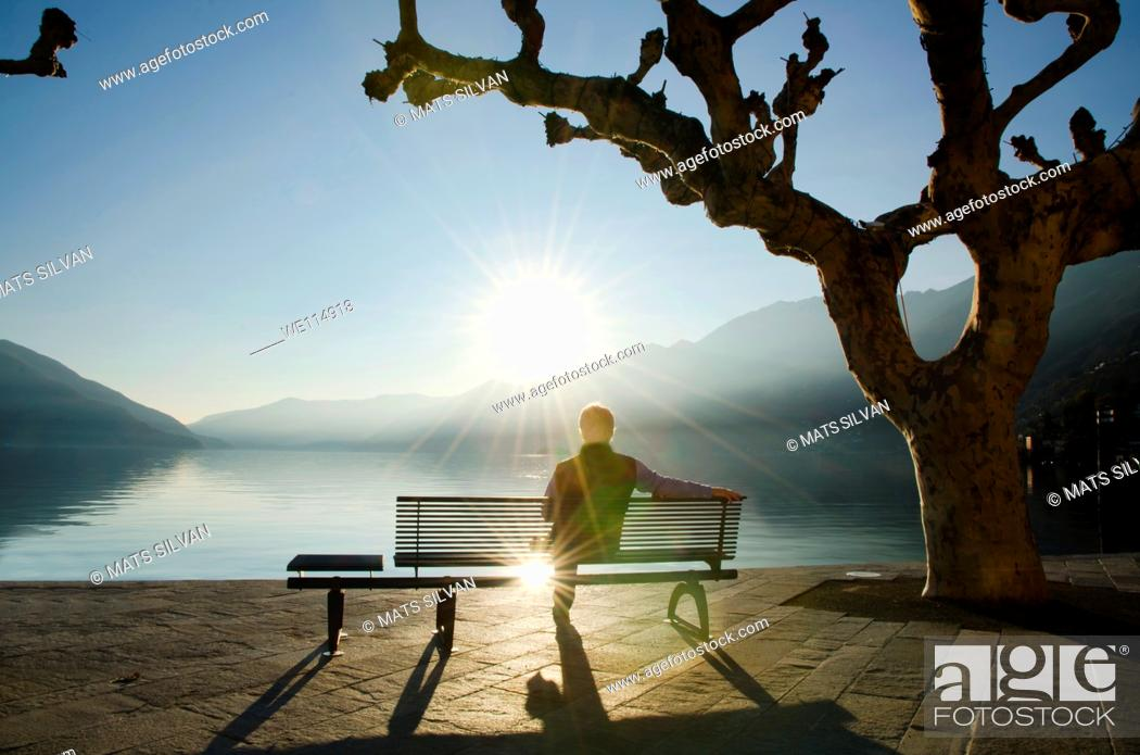 Stock Photo: Man sitting on a bench and watching a sunset on alpine lake Maggiore with mountain in Ascona, Switzerland.