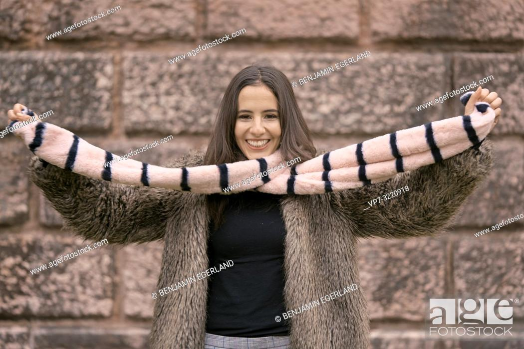 Photo de stock: fashionable woman playing with scarf, happy laughing, in Munich, Germany.