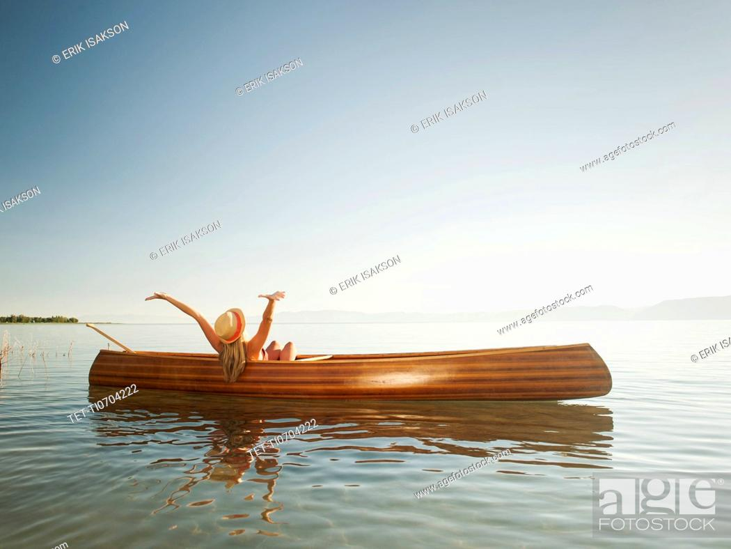 Stock Photo: Young woman relaxing in canoe with arms raised.