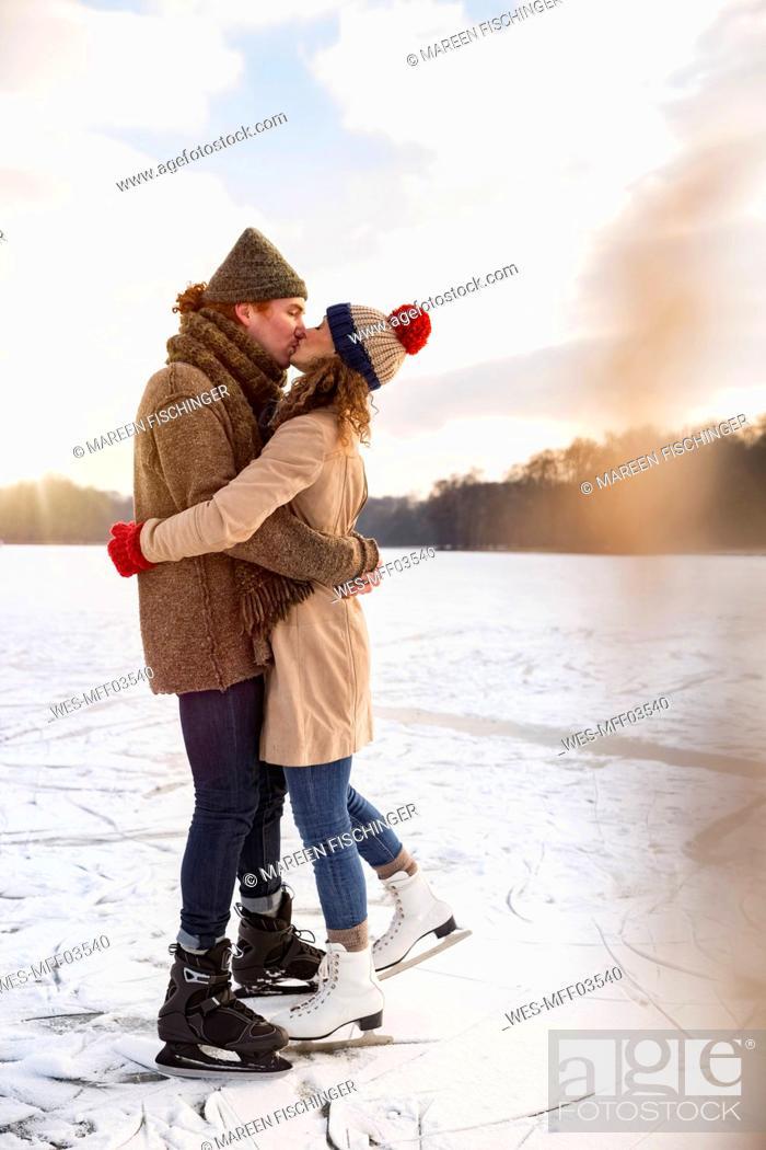Stock Photo: Couple with ice skates kissing on frozen lake.
