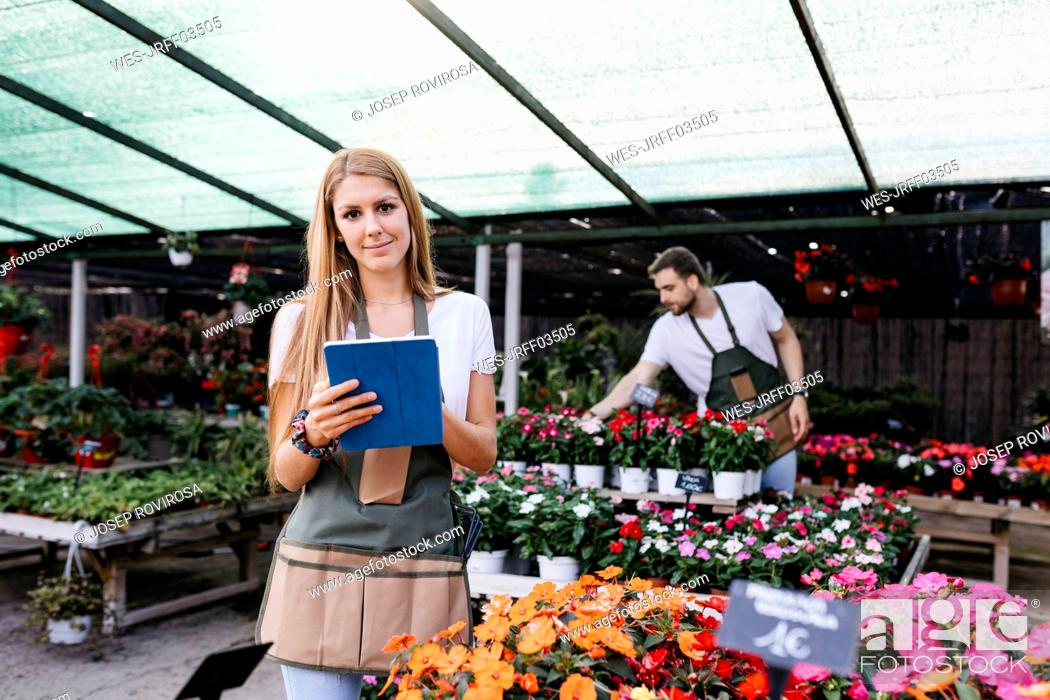 Stock Photo: Portrait of a smiling female worker in a garden center using a tablet.