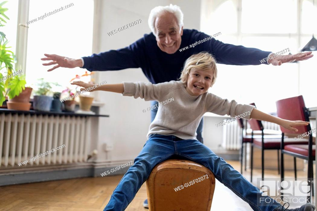 Stock Photo: Happy grandfather and grandson playing with buck at home.