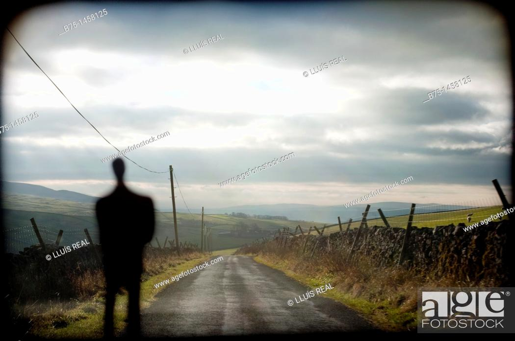 Stock Photo: Silhouette of man in front of a country road.