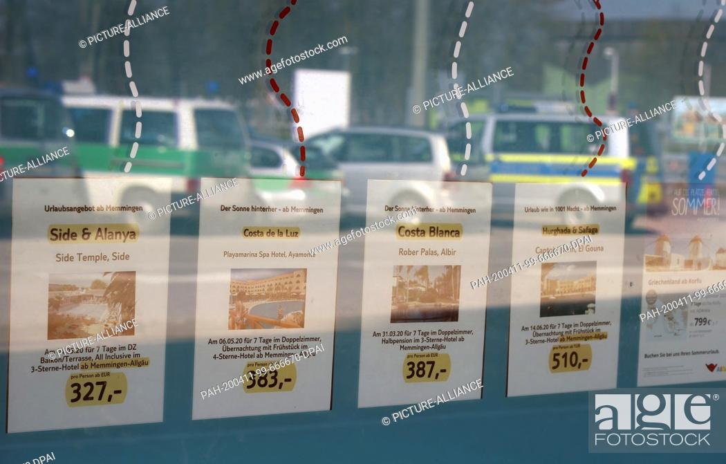 Stock Photo: 08 April 2020, Bavaria, Memmingen: In a window in which police cars are mirrored, advertising for air travel is carried out at the closed Allgäu-Airport.