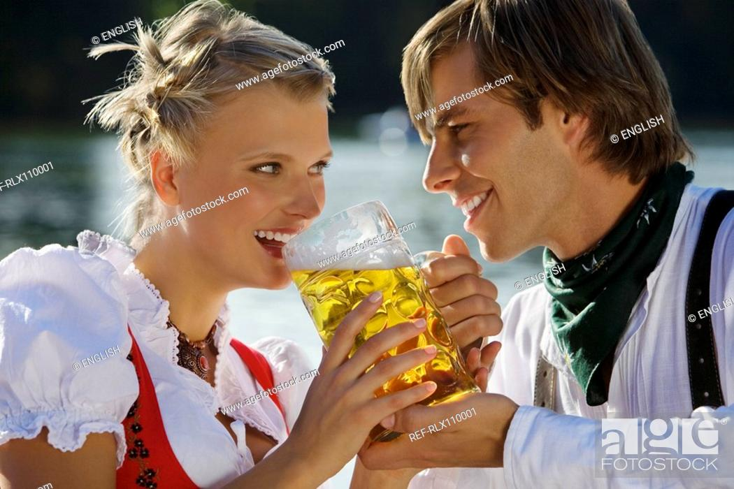 Stock Photo: Young couple in traditional Bavarian outfit, sharing beer in beer garden, Munich.