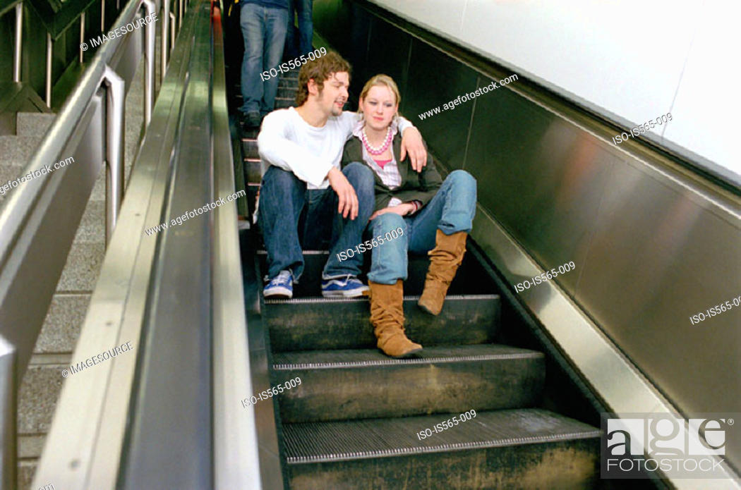 Stock Photo: Couple sitting on escalator.