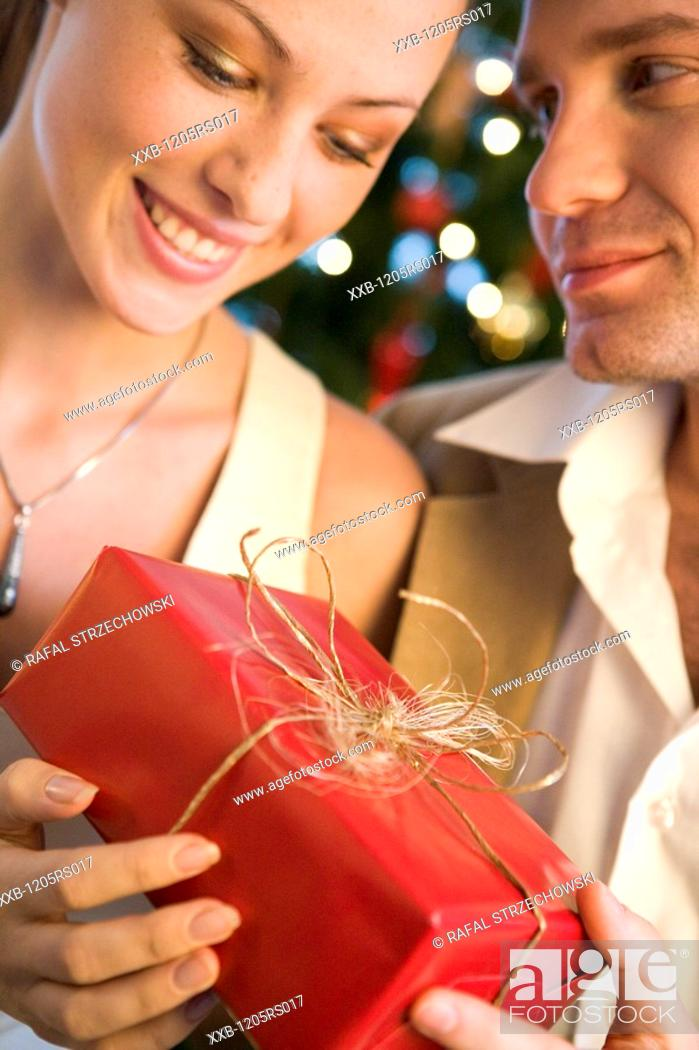Stock Photo: couple giving themself christmas presents.