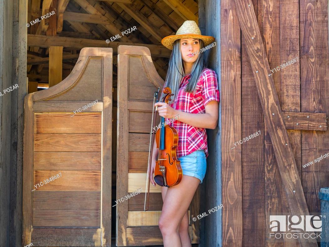 Stock Photo: Teen girl violin player American West saloon.