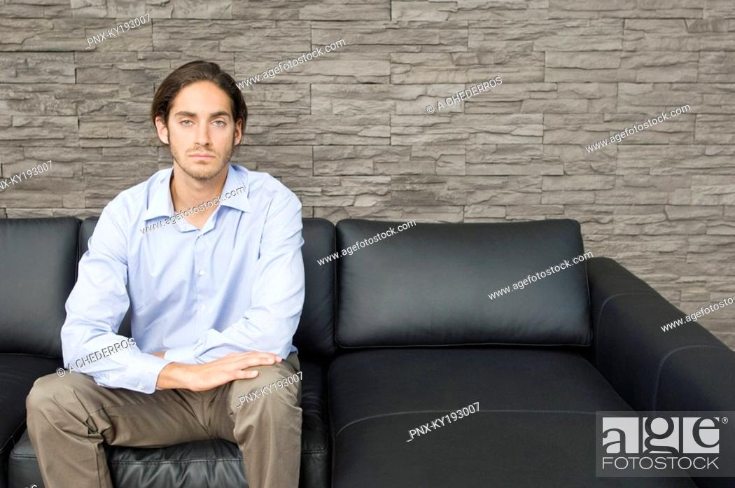 Stock Photo: Man sitting on a couch.
