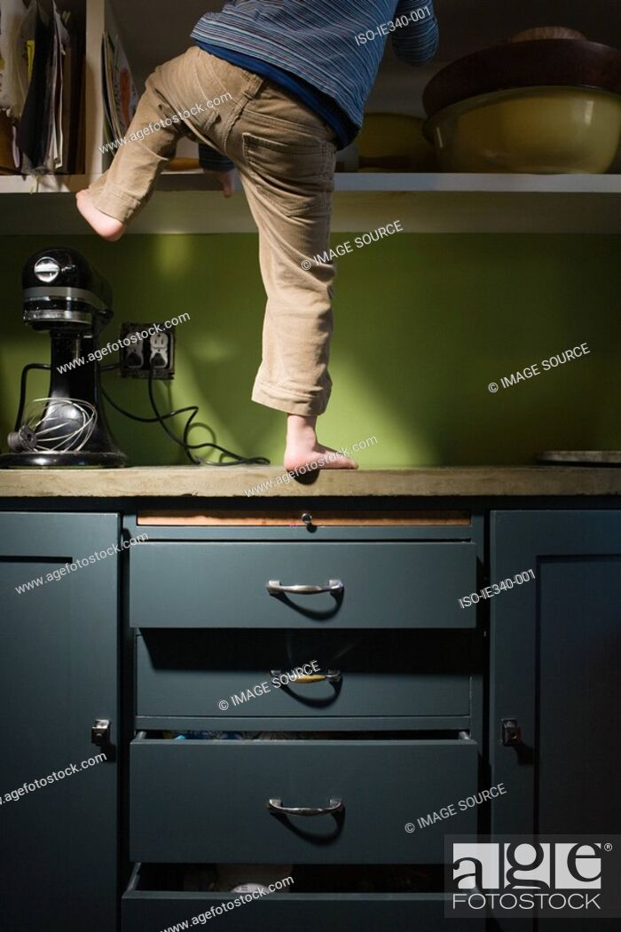 Stock Photo: Boy climbing in kitchen.