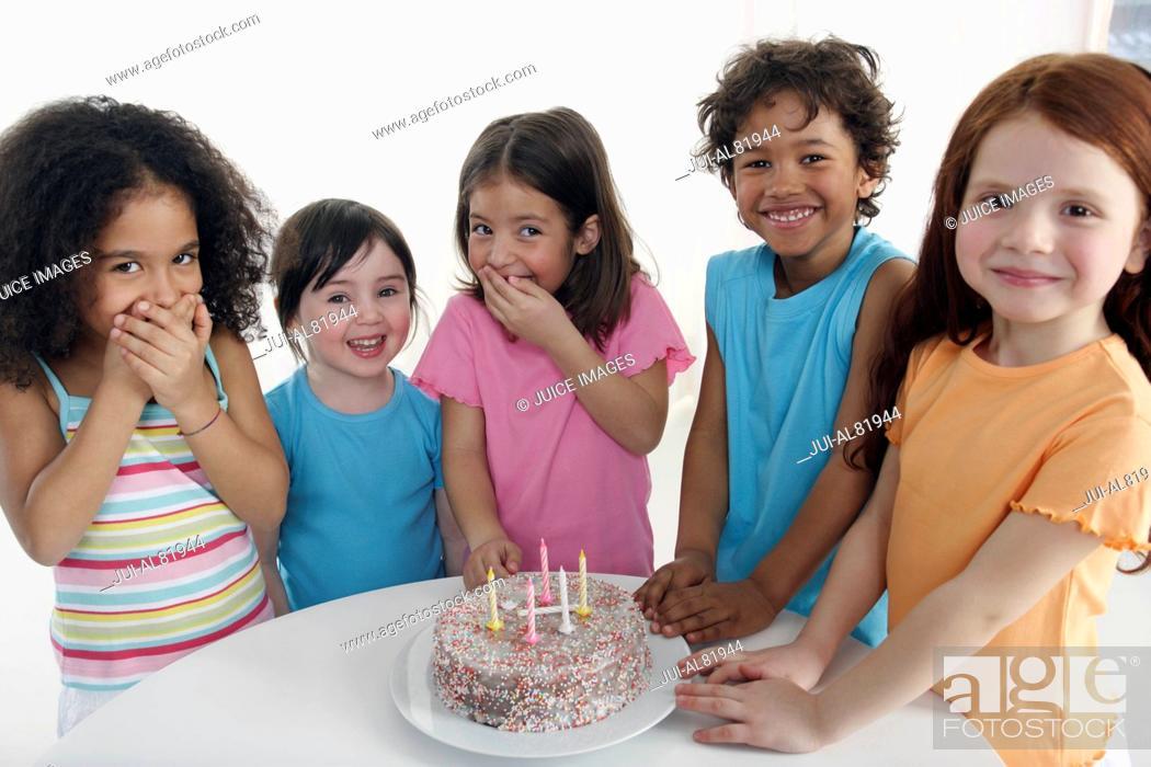Stock Photo: Group of children smiling around birthday cake indoors.