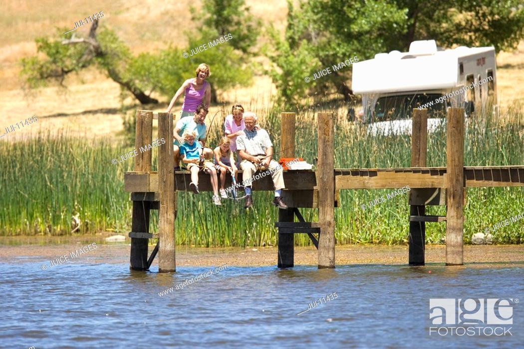 Stock Photo: Family of three generations fishing from jetty, motor home in background, low angle view.