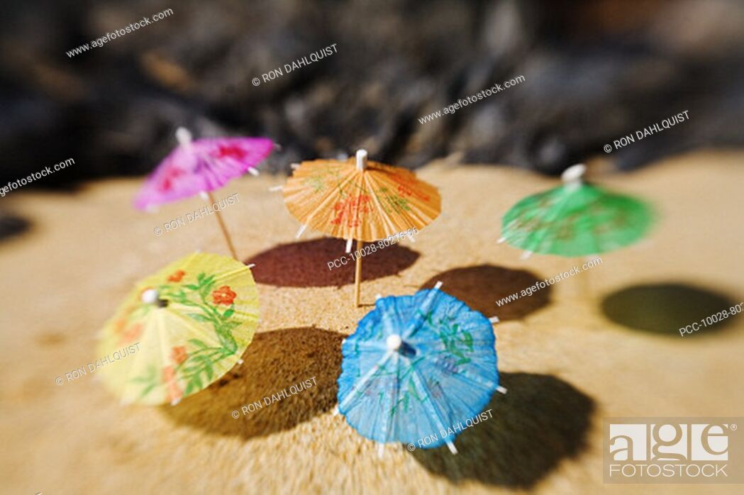 Stock Photo: Colorful cocktail umbrellas stuck in the sand of a tropical beach.