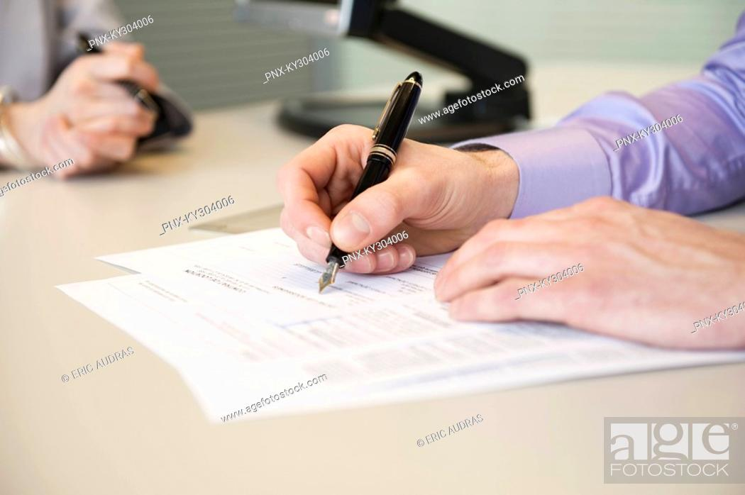 Stock Photo: Man signing documents.
