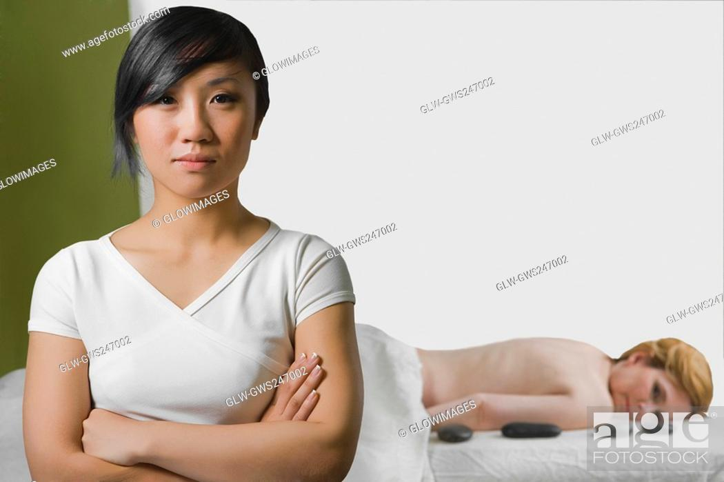 Stock Photo: Close-up of a massage therapist with a mature woman lying on a massage table behind her.